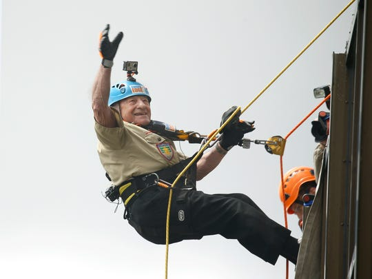 89-year-old Joe Aiello of Henrietta waves to friends as he starts to rappel down the side of the First Federal Plaza Building.