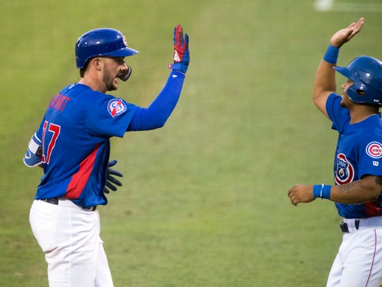 Kris Bryant, left, is welcomed to the dugout by the Smokies' Charcer Burks after Bryant homered Monday.