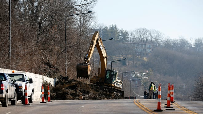 A road crew attempts to clear mud and debris from the Westbound lane of Columbia Parkway between Torrence and Kemper in Cincinnati on Friday, Feb. 5, 2016. Mudslides are common along the route following rain and snow storms.