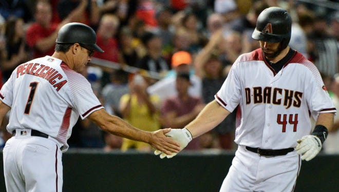 Paul Goldschmidt celebrates with third base coach Tony Perezchica (1) after his two-run home run in the first inning against the Los Angeles Dodgers at Chase Field.