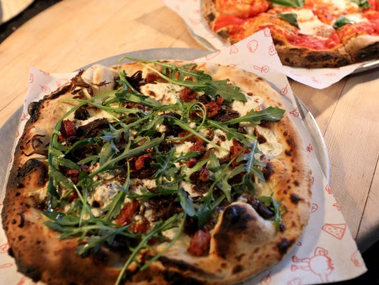 Three cheese pizza topped with arugula from Papa Rosso,