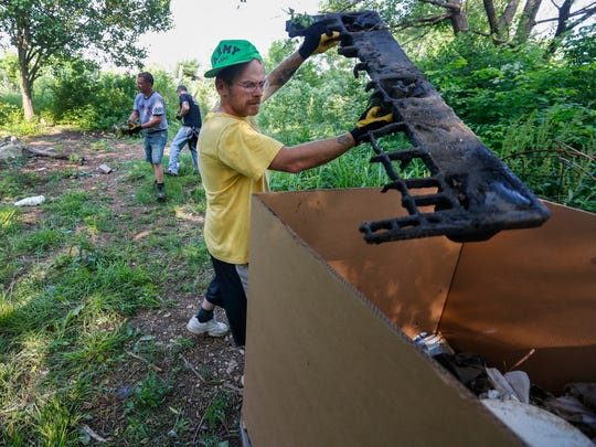 Michael Rubatt throws trash into a box while cleaning up the former homeless camp near Kearney Street east of Glenstone Avenue on Saturday, May 19, 2018.