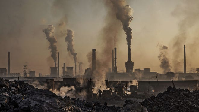 Smoke billows from a large steel plant as a Chinese labourer works at an unauthorized steel factory, foreground, on Nov. 4, 2016, in Inner Mongolia, China.