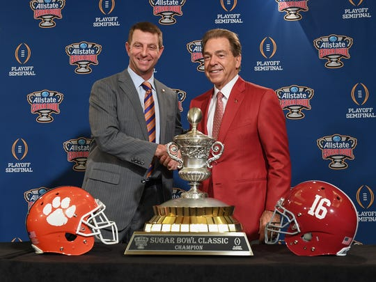 Clemson head coach Dabo Swinney, left, shakes hands with Alabama head coach Nick Saban after they posed in front of the Sugar Bowl trophy in New Orleans on Sunday, December 31, 2017.