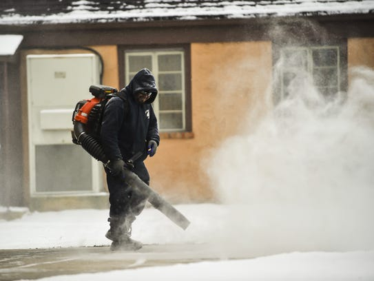 A worker blows snow from the sidewalk of Our Lady of