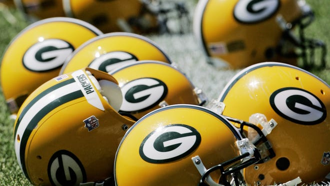 Green Bay Packers helmets are lined up on the practice field.