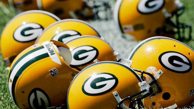 Green Bay Packers helmets are lined up on the field during training camp.