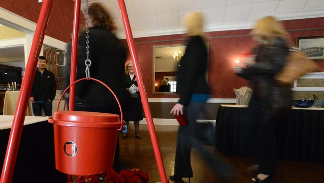 People walk past an iconic Salvation Army red kettle Tuesday morning, Nov. 14, 2017, at the Lancaster Country Club in Hocking Township. The Salvation Army in Fairfield County kicked off it's annual fundraiser during Tuesday's event.