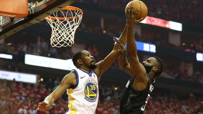 Houston Rockets guard James Harden (13) shoots against Golden State Warriors forward Kevin Durant (35) during the first quarter in game one of the Western conference finals of the 2018 NBA Playoffs at Toyota Center.