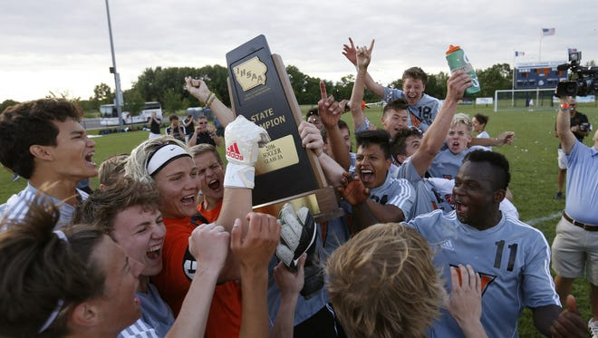 Members of the West Des Moines Valley team lift up their state championship trophy Saturday, June 4, 2016, after defeating Iowa City High in the finals of the 3A boys state soccer tournament in Des Moines.