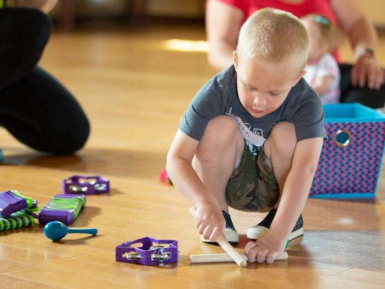 Seth Pogue, 2, plays with various musical instruments during a Zumbini class in Las Cruces. The program allows children ages 0-4 to to spend time with their caregivers while enhancing their cognitive, emotional, social and motor skills.