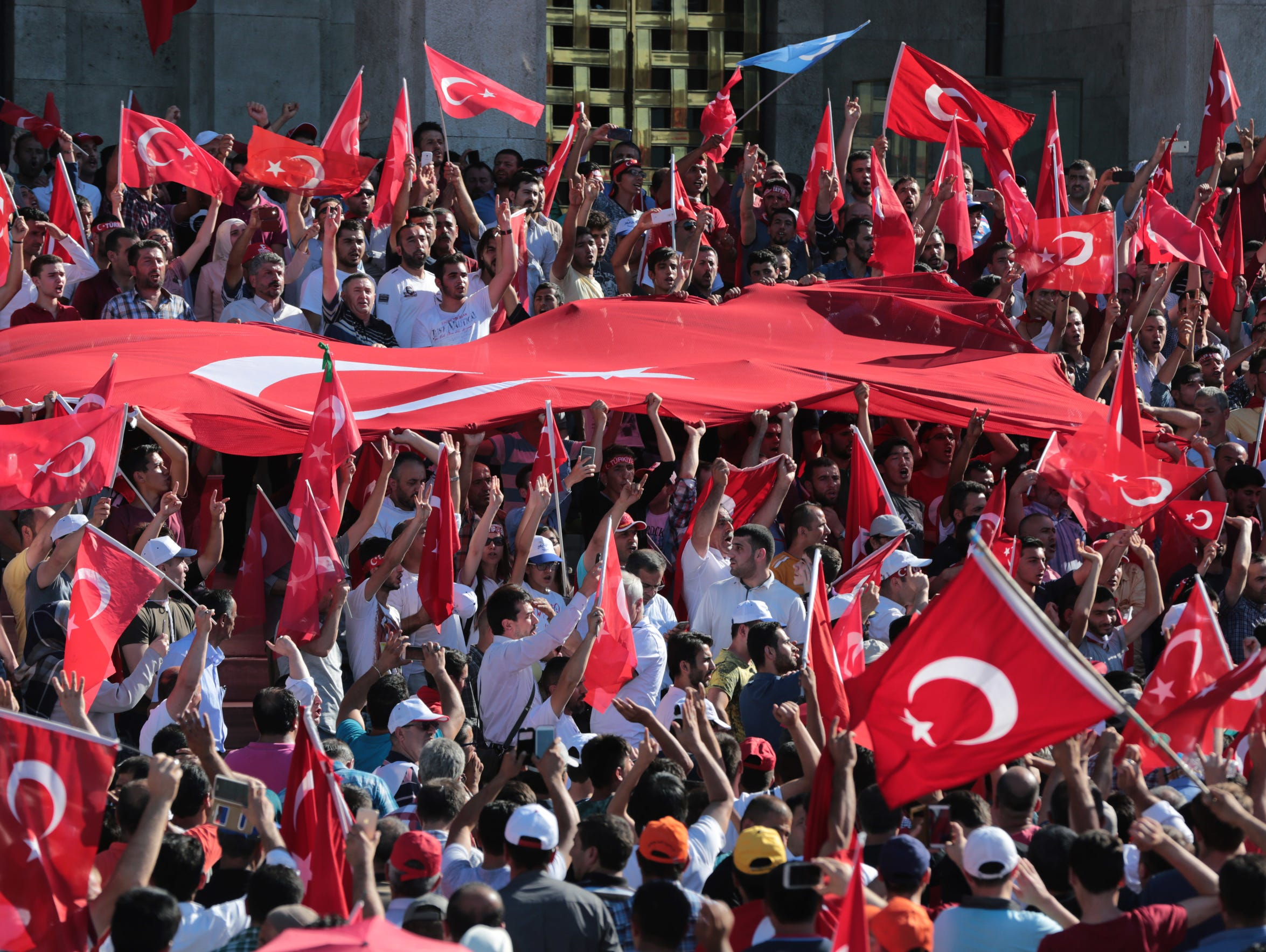 Turkish citizens wave their national flags as they