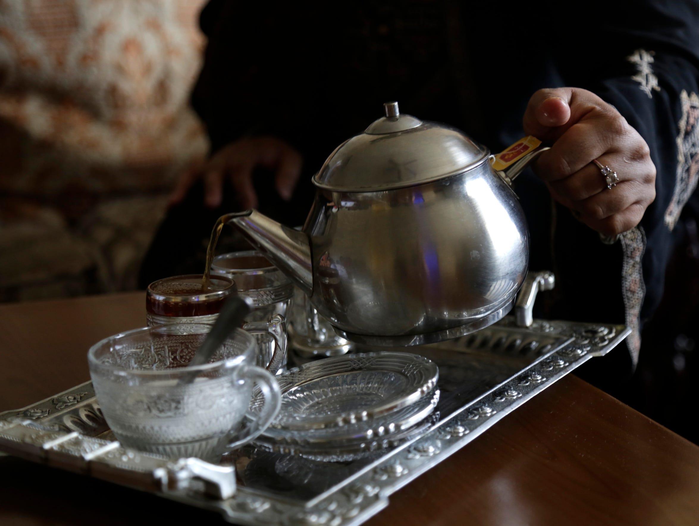 Rasha Almasri pours a cup of cardamom scented tea at