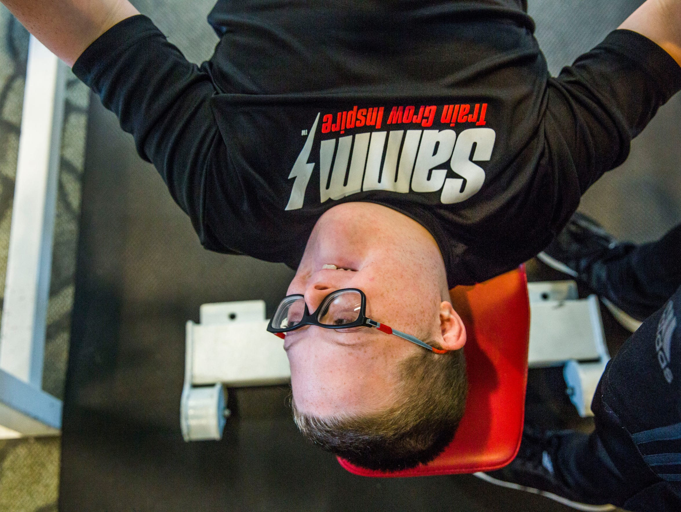 Parker Seward, 13, does a bench press with the help