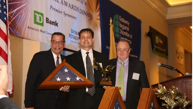 John Magnifico, left, of the Newark Liberty Airport Marriott and chairman of the board of the Gateway Regional Chamber of Commerce, presents the Large Company of the Year award to Neil Spracklen, center, of Linden-based Phillips Bayway Refinery, as Glenn Nacion of Trinitas Regional Medical Center looks on. The award was presented Feb. 7 at the Chamber's 105th Annual Dinner Meeting at the Marriott.