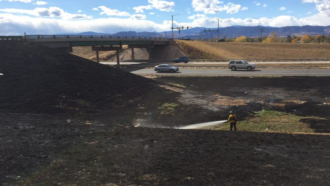Firefighters mop up a small fire near Prospect Road and Interstate 25 on Wednesday. They responded to at least three small fires along I-25.