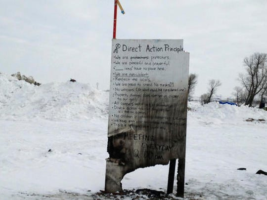 A sign is seen at an encampment set up near Cannon Ball, N.D., Wednesday, Feb. 8, 2017, for opponents against the construction of the Dakota Access pipeline. Opponents have called for protests around the world Wednesday, Feb. 8, 2017, as the Army prepared to green-light the final stage of the $3.8 billion project's construction. The Army said Tuesday, Feb. 7, that it will allow the four-state pipeline to cross under a Missouri River reservoir in North Dakota, the last big chunk of construction.