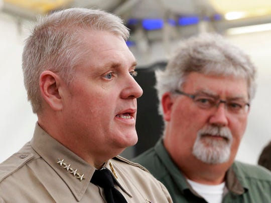 FILE - In this Feb. 14, 2017, file photo, Butte County Sheriff Kory Honea, left, answers a question concerning his decision to lift the evacuation order and allow people to return home, as Bill Croyle, acting director of the Department of Water Resources, right, looks on during a news conference in Oroville, Calif. Over six straight days, the operators of the Oroville Dam had been saying there was no immediate danger after water surging down the main spillway gouged a hole the size of a football field in the concrete chute. But now suddenly they realized that the dam's emergency backup spillway — essentially an unpaved hillside — was falling apart, too, and could unleash a deadly torrent of water. Honea reacted by ordering the immediate evacuation of nearly 200,000 people downstream.