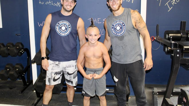Max DiTondo, Marc Nantel and Joe Coyne pose for a photo after Nantel became the first 9-year-old to bench press 100 pounds.