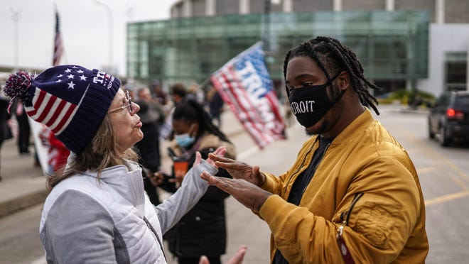 Angelo Austin (right) of Detroit asks a Trump supporter to back away from him since she wasn't wearing a mask as Trump supporters gathered outside of the TCF Center in Detroit on Thursday, Nov 5, 2020 where the absentee ballot count for the city of Detroit occurred.