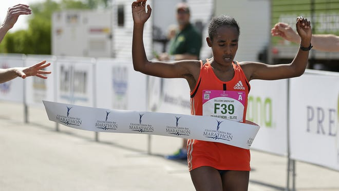 Worknesh Oda raises her arms as she crosses the finish line to win the women's Cellcom Green Bay Marathon in Green Bay on Sunday, May 22, 2016.