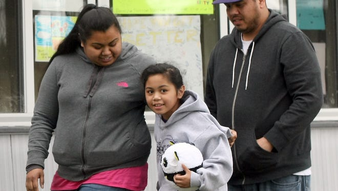 Amina Kocer-Bowman, then 9, with her parents Teri and John after she was released from Harborview Medical Center and returned home in April 2012.