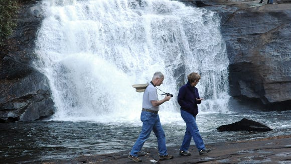 Hikers walk along Triple Falls Trail in DuPont State