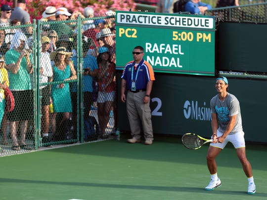 Fans watch as Rafael Nadal of Spain practices on court