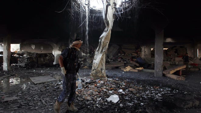 A Yemeni inspects the rubble of a destroyed building following reported airstrikes by Saudi-led coalition air-planes on the capital Sanaa on October 8, 2016.
