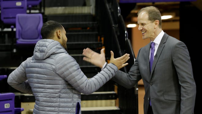 New Washington coach Mike Hopkins (right) greets returning guard David Crisp last month at his introductory news conference.