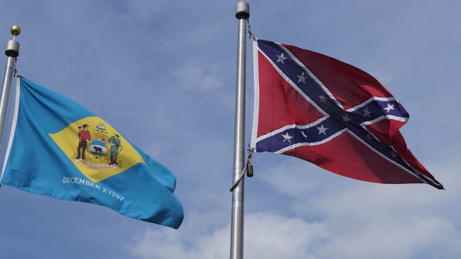 The Confederate flag flies alongside the Delaware state flag over the Delaware Confederate Monument. Officials say there are no plans to remove the flag, which has been taken from several sites across the country following the shooting at a South Carolina church.
