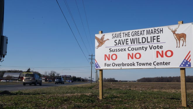 A property owner's sign urges opposition to the Overbrook Town Center, proposed for land here along Highway One, across from Cave Neck Road and not far from Milton. The project's developer has reactivated a land-use request with Sussex County government.