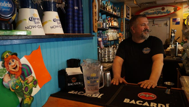 Steve Cannon tends bar Monday at the Frogg Pond in Rehoboth Beach. The bar has planned Tuesday menu specials and live entertainment for St. Patrick's Day.