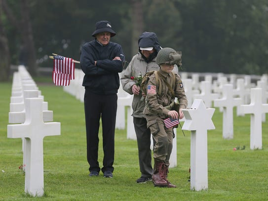 David Chamberlain, left, grandfather Charly Powers and his son Steve, from Atlanta, pay their respect by placing a U.S. flag on the grave of a U.S. soldier who died during World War II at the Colleville American military cemetery in France on June 6, 2018, the 74th anniversary of the D-Day landing.