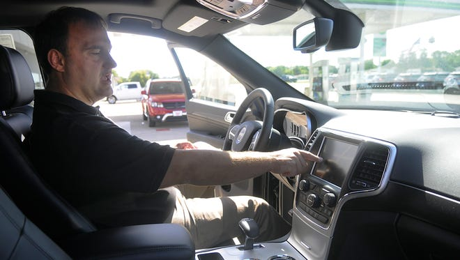 A.M. Maus & Son owner Steve Maus talks about the Uconnect system in a 2015 Jeep Grand Cherokee on Tuesday at his dealership in Kimball. Uconnect links vehicles to smartphones and the Sprint cellular network. Remote-control issues prompted a recent security update.