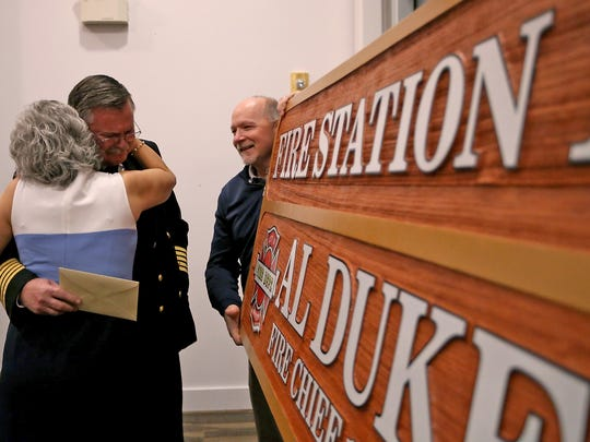 Bremerton Fire Chief Al Duke gets a hug from his wife Amy after a sign naming Fire Station 1 in his honor was presented at his retirement party on Friday, Jan. 27, 2017.