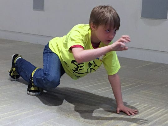 A Glen Acres Elementary School student visiting from Pennsylvania plays charades, acting out the motions of an endangered animal as part of an Earth Day activity at the Delaware Museum of Natural History.