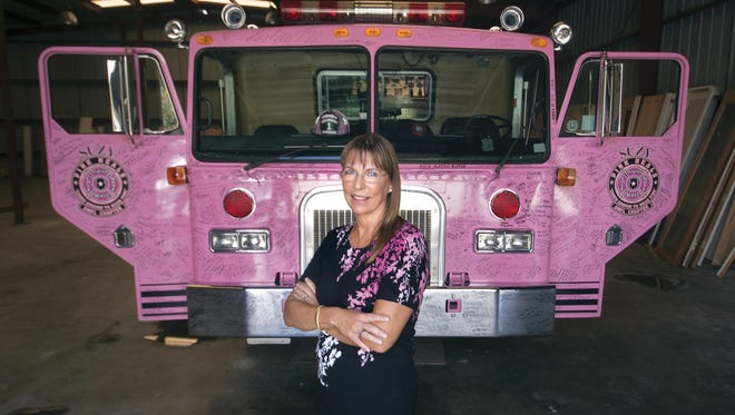 Susan Lewis of Pink Heals of Southwest Florida with one of the organization's pink fire trucks.  They use the trucks to raise money and promote awareness. The  organization  supports woman and families affected by cancer.