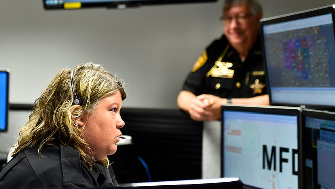 Officer Heidi Neagles sets up at her new station in the new Dispatch Center in the County Building.