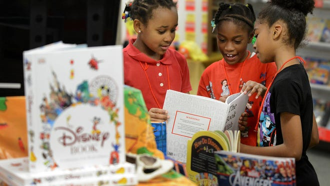 Pope Elementary third-graders Alece Davis, Zykia Cole, and Trista Owens look at books on sale during a scholastic book fair Tuesday, Oct. 25.