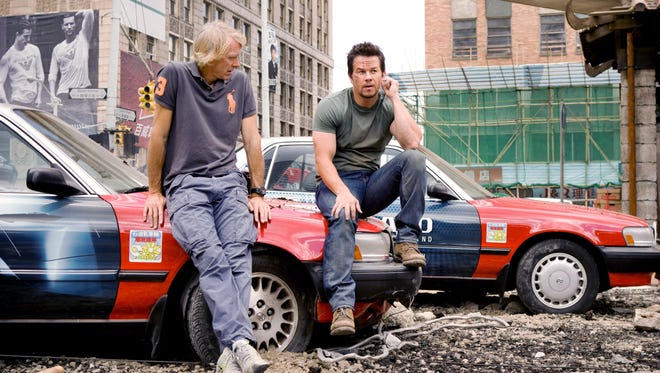 "In a photo provided by Paramount Pictures, Director/Executive Producer Michael Bay, left, discusses a scene with Mark Wahlberg (who plays Cade Yeager) on the Detroit set of ""Transformers: Age of Extinction."""