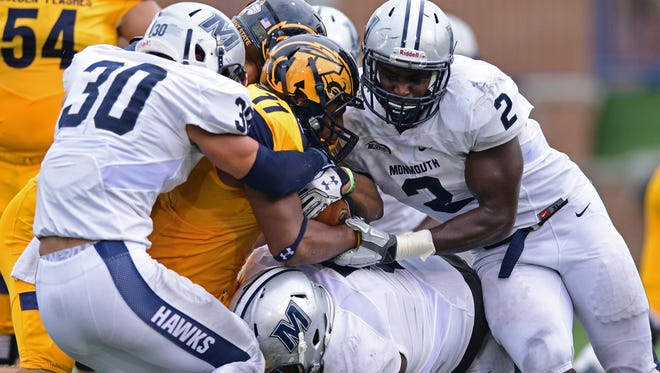 Mike Basile (30) and Darnell Leslie (2) make a tackle during the first half of Monmouth University's loss at Kent State