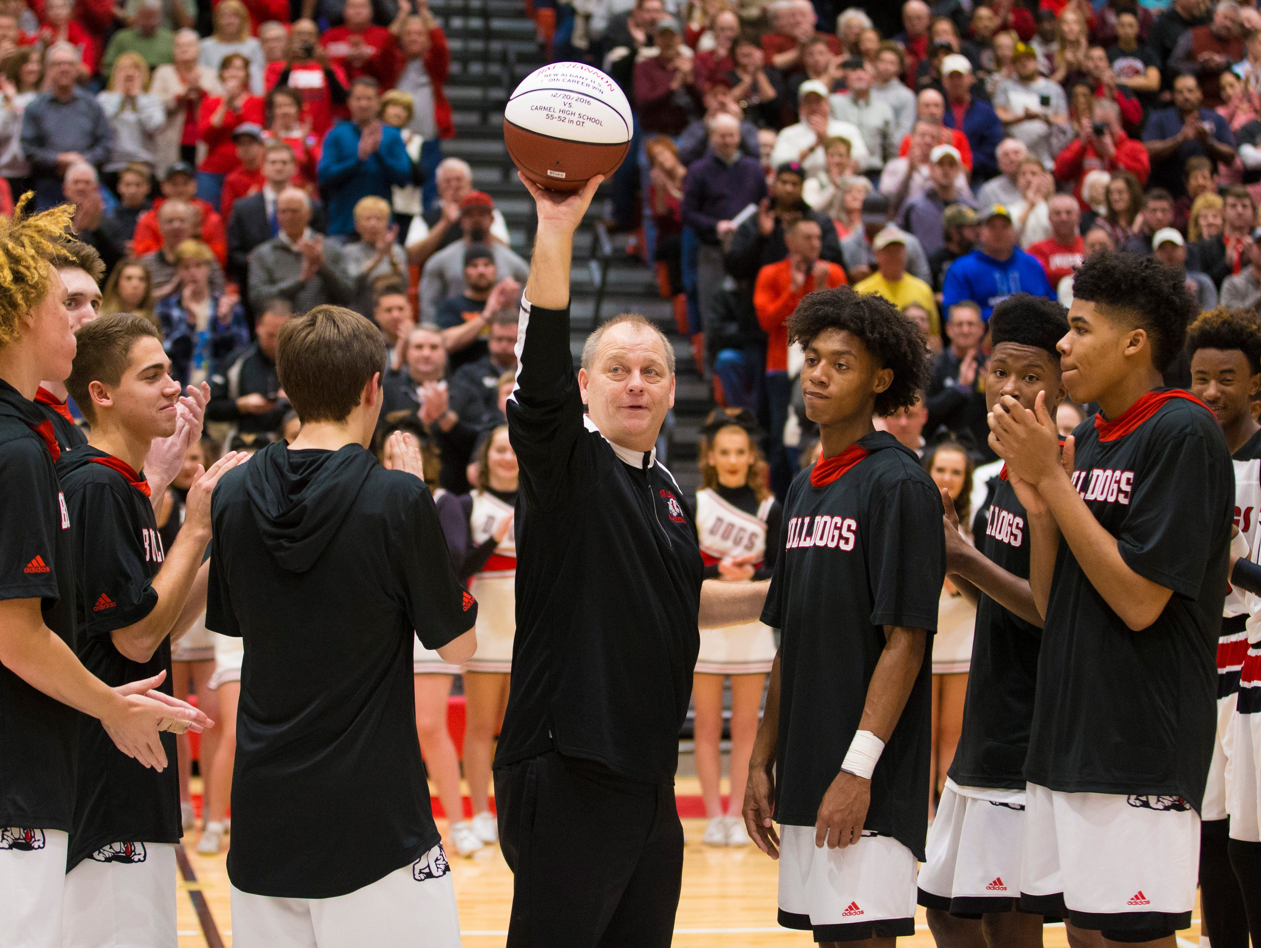 New Albany head coach Jim Shannon holds up a ball honoring his 500th career win as a head coach in Indiana.