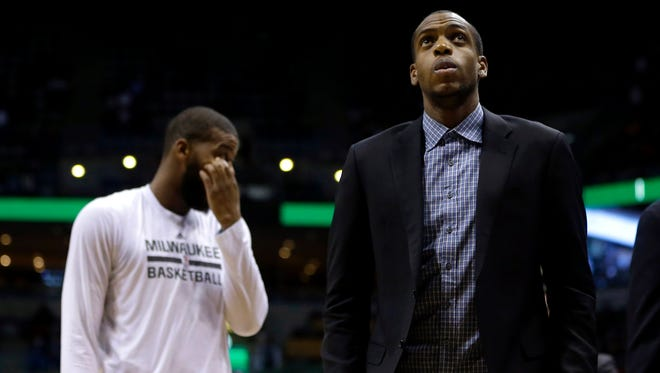 Milwaukee Buck Khris Middleton, (right), looks up to the scoreboard from the bench during an NBA basketball game against the Brooklyn Nets Dec. 3.