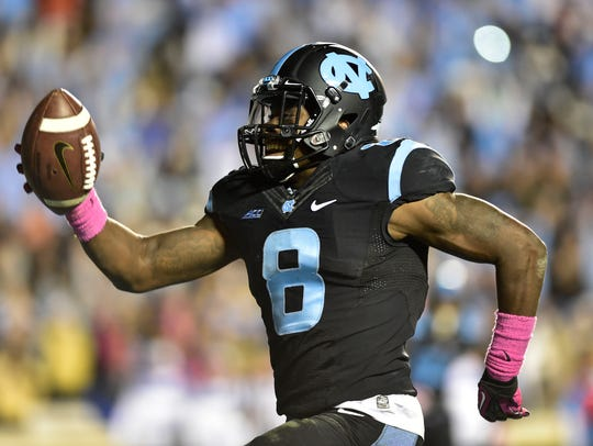 North Carolina running back T.J. Logan (8) scores the