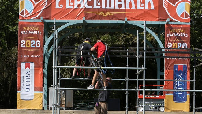 Little Rock City Staging's Mike Curtis, from left, Jeremy Josephson and Travis Green build the front of house, Thursday, July 23, 2020, for the weekend Peacemaker music festival at Fort Smith's Riverfront Park.