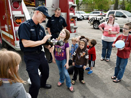 St. Cloud firefighter Todd Cariveau demonstrates how the spray nozzle on the end of a hose works during a Memorial Day parade Saturday around Lake George.