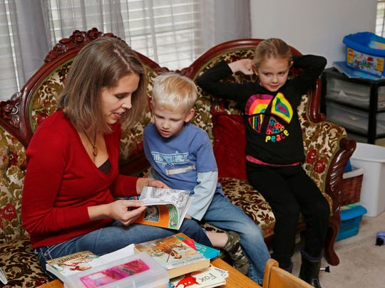 Cara Putman reads to her son Daniel, 4, while daughter Rebecca, 6, looks on Monday, November 24, 2014, in their Lafayette home. An upstairs room in the Putman home serves as the homeschooling classroom for all four of Putman's children.