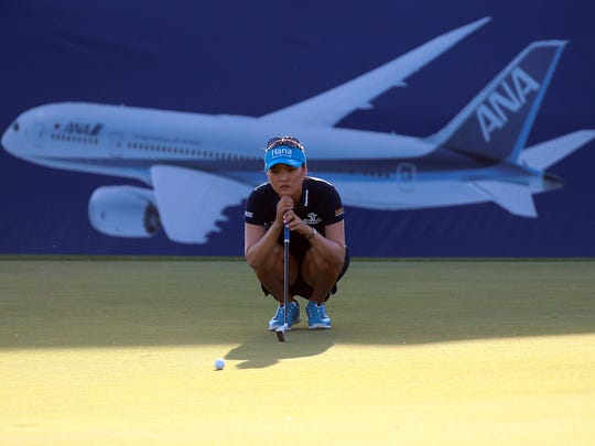 An All Nippon Airways airliner is pictured on the grandstand wrap along the eighteenth green as So Yeon Ryu of South Korea reads her putt on Thursday, April 2, 2015 during the ANA Inspiration at Mission Hills Country Club in Rancho Mirage, Calif. Ryu is one of four players tied for third place at -3 and two strokes behind first round leader Morgan Pressel.