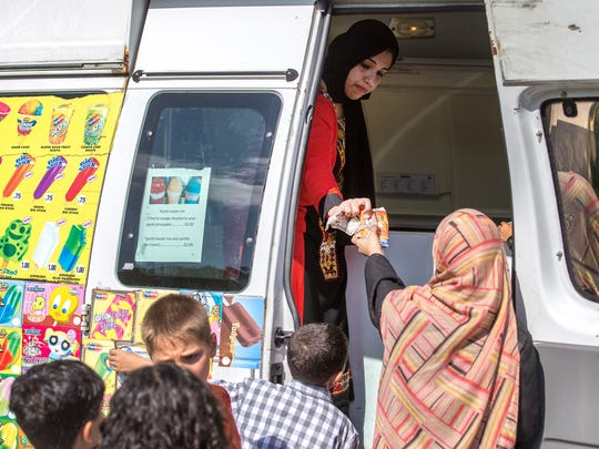 Samar Syed serves ice cream to children from an ice cream truck during Eid al-Fitr celebrations in Bear on Monday.